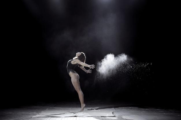 Ragazza che balla con una farina sul nero Foto Premium