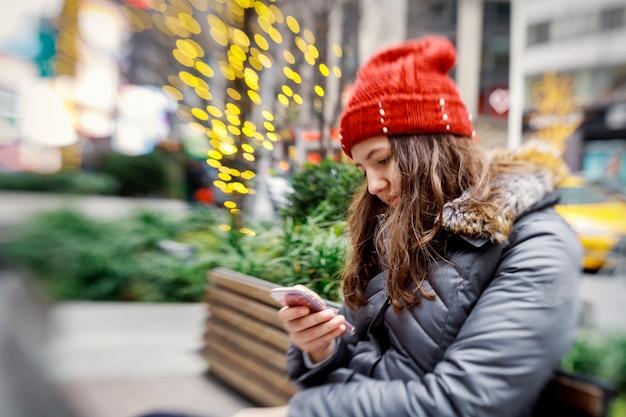 Ragazza che cammina e manda un sms sul suo smartphone Foto Premium