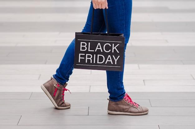 Ragazza che cammina intorno al centro commerciale con una borsa. venerdì nero. Foto Premium