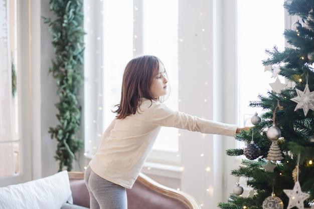 Ragazza che decora la casa con albero di natale e decorazioni natalizie. Foto Premium