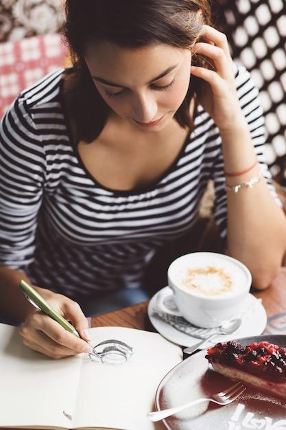 Ragazza che disegna una tazza di caffè nel taccuino Foto Gratuite