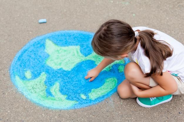 Ragazza che disegna una terra del globo con gesso sull'asfalto Foto Premium