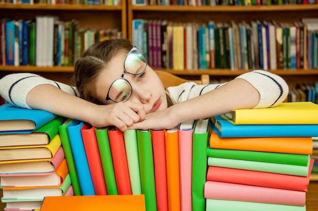 Ragazza che dorme sui libri in biblioteca Foto Premium