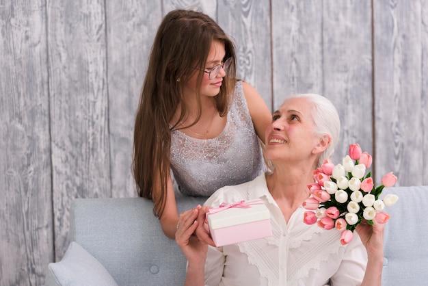 Ragazza che esamina sua nonna che tiene il contenitore di regalo e il mazzo del fiore del tulipano in mani Foto Gratuite