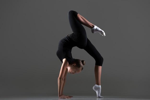 Ragazza che fa verticale con una gamba sul pavimento Foto Gratuite