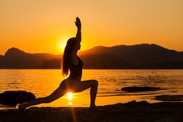 Ragazza che fa yoga dall'oceano. Foto Premium