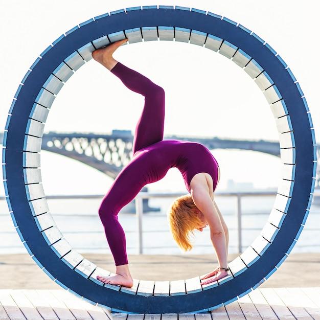 Ragazza che fa yoga in un anello sulla spiaggia Foto Premium