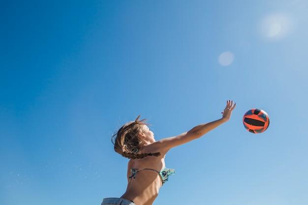 Ragazza che gioca a beach volley vista dal basso Foto Gratuite