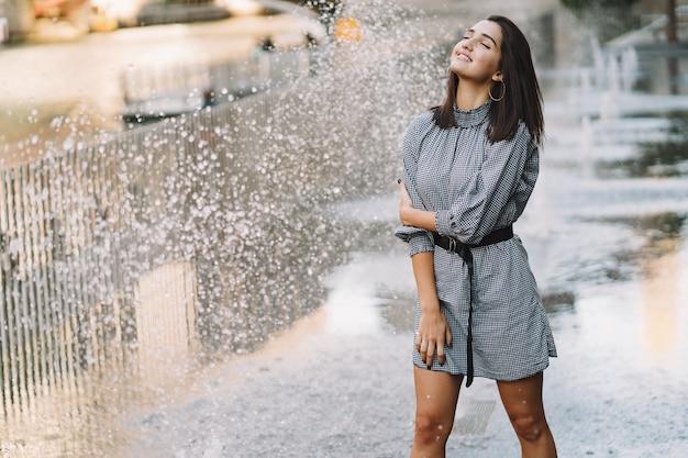 Ragazza che gioca e balla in giro su una strada bagnata Foto Gratuite
