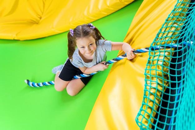 Ragazza che gioca nel trampolino centrale che salta e che si arrampica con la corda Foto Premium