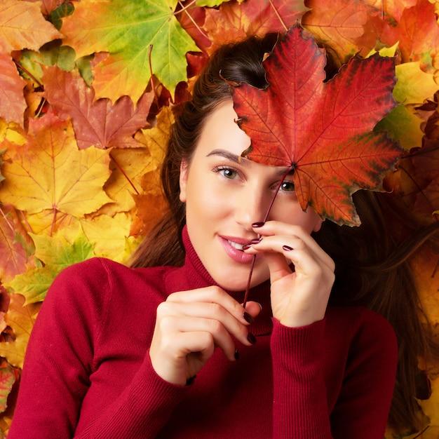 Ragazza che giudica la foglia di acero rossa disponibila sopra il fondo variopinto delle foglie cadute. Foto Premium