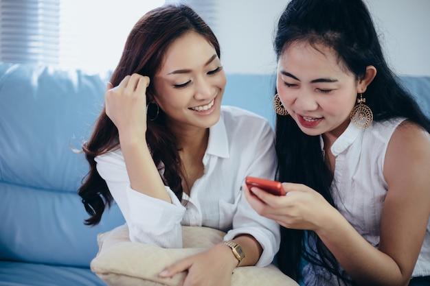 Ragazza che guarda al telefono del suo amico e sentirsi eccitante e sorridente Foto Premium