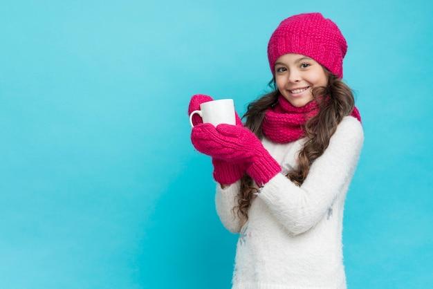 Ragazza che indossa abiti invernali e tenendo la tazza di tè Foto Gratuite