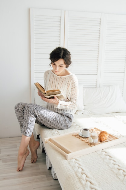 Ragazza che legge un libro a colazione Foto Premium