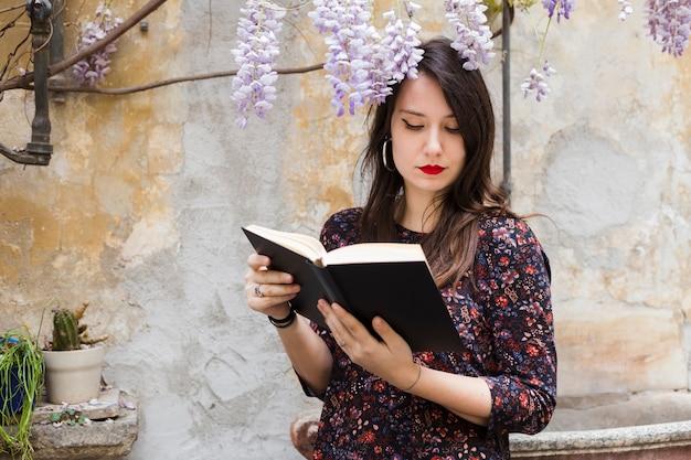 Ragazza che legge un libro in strada Foto Gratuite