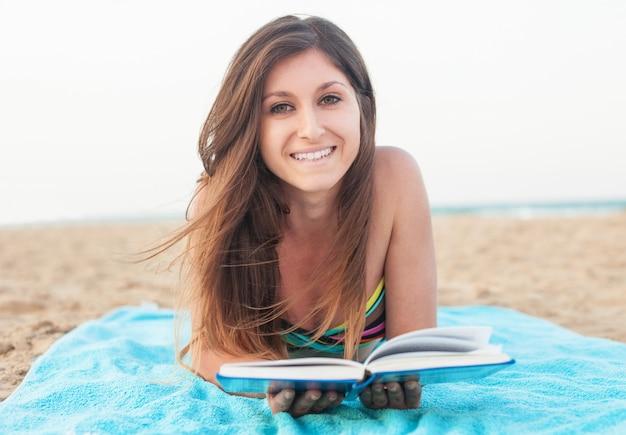 Ragazza che legge un libro sulla spiaggia Foto Gratuite