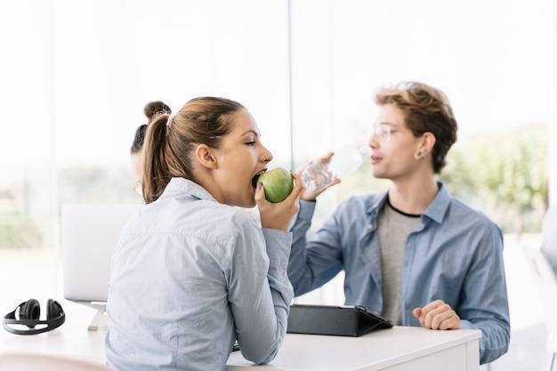 Ragazza che mangia mela ad un tavolo con altre persone Foto Premium