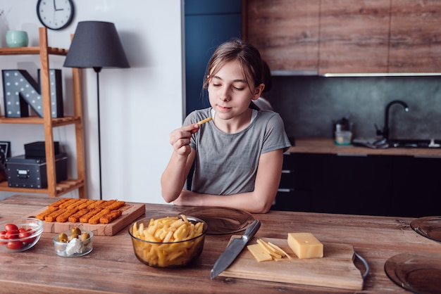 Ragazza che mangia patatine fritte Foto Premium