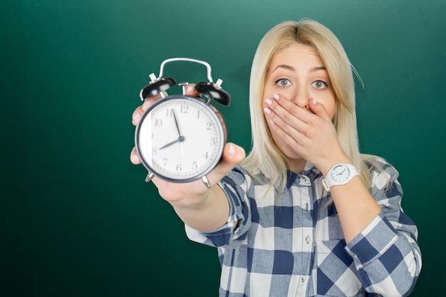 Ragazza che mostra orologio sopra bordo nero Foto Premium