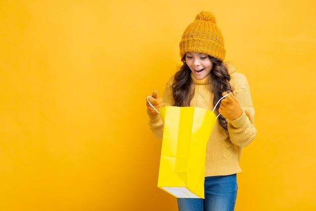Ragazza che osserva in sacchetto della spesa giallo Foto Gratuite