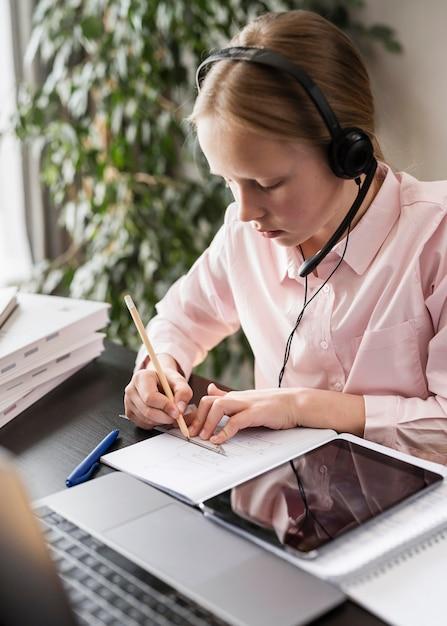 Ragazza che partecipa a una lezione online mentre prende appunti Foto Gratuite