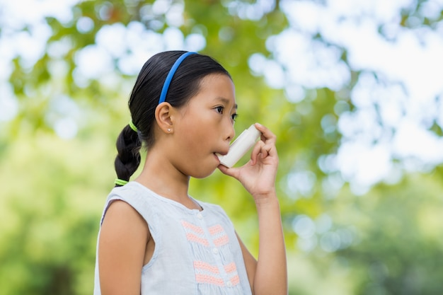 Ragazza che per mezzo di un inalatore per l'asma Foto Premium