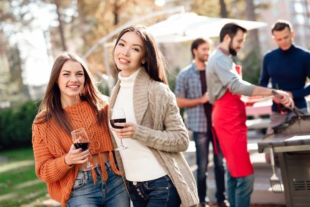 Ragazza che posa alla macchina fotografica con vino durante il picnic. Foto Premium