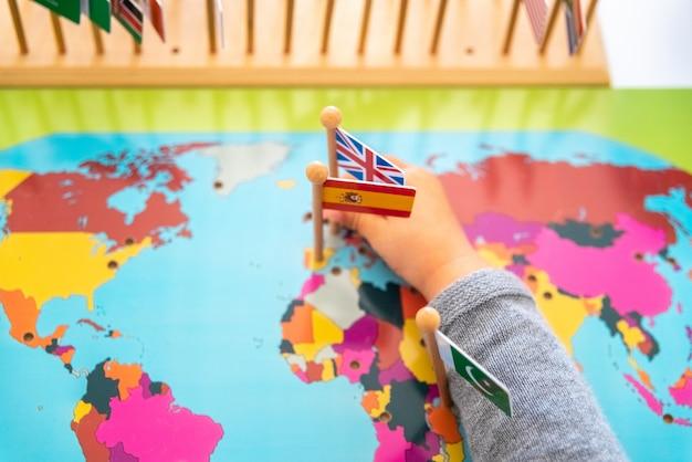 Ragazza che posiziona le bandiere di europa e spagna su una mappa Foto Premium