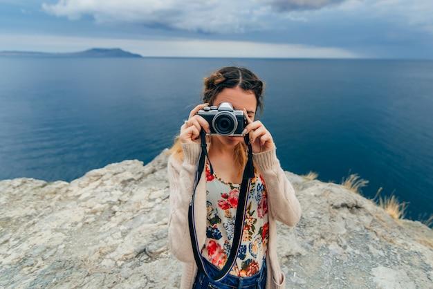 Ragazza che prende le immagini all'aperto su una retro macchina fotografica sulle vacanze estive Foto Premium
