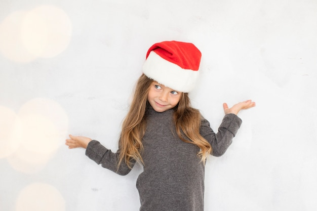 Ragazza che propone modo con un cappello di babbo natale Foto Gratuite