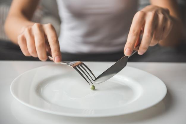 Ragazza che prova a mettere un pisello sulla forcella. concetto di dieta Foto Premium