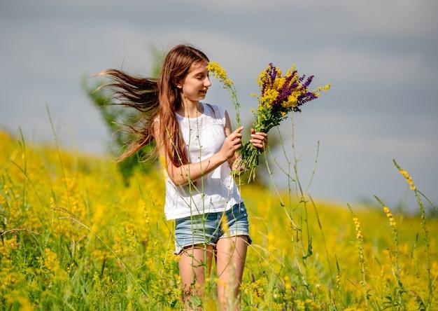 Ragazza che raccoglie i fiori sul campo Foto Premium