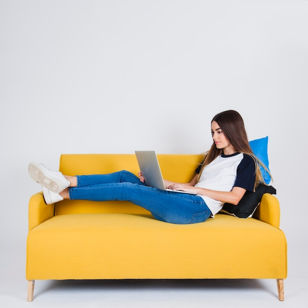 Ragazza che sfoglia il nastro sul divano scaricare foto for Divano gratis