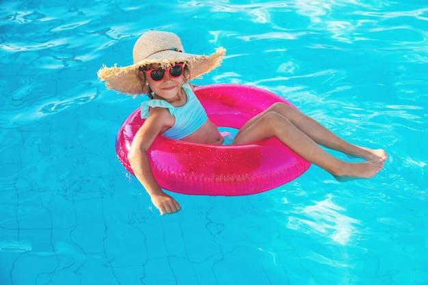 Ragazza che si distende nella piscina Foto Premium