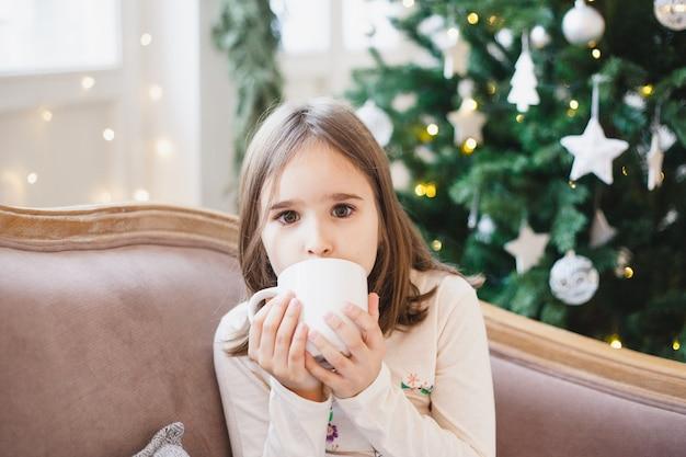 Ragazza che si siede e che beve tè o un drink da una tazza bianca Foto Premium