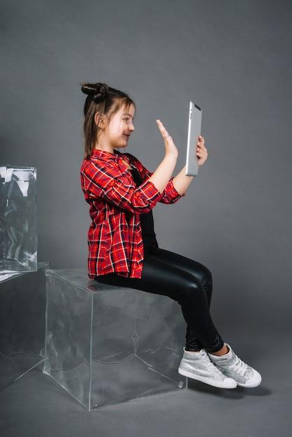 Ragazza che si siede sul blocco che ha video chiamata tramite la mano d'ondeggiamento del ridurre in pani del pc Foto Gratuite