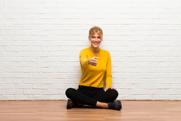 Ragazza che si siede sul pavimento che agita le mani per la chiusura del buon affare Foto Premium