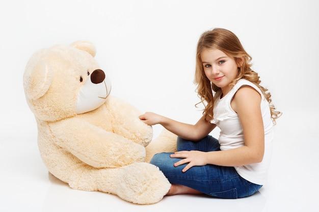 Ragazza che si siede sul pavimento con l'orso del giocattolo che tiene la sua zampa. Foto Gratuite