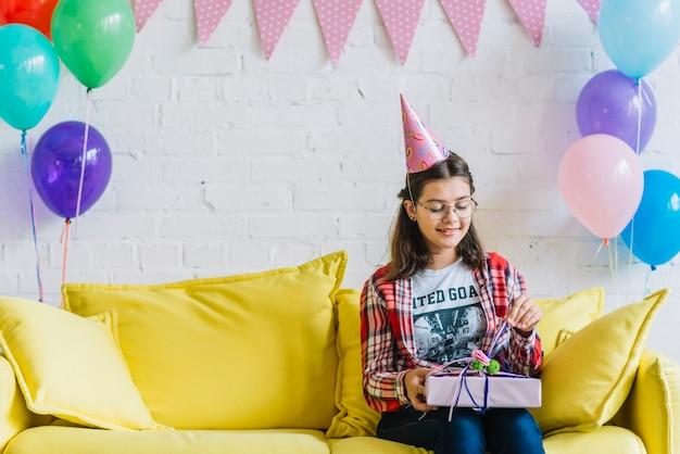 Ragazza che si siede sul regalo di compleanno di unwrapping del sofà Foto Gratuite