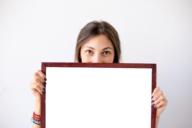 Ragazza che sorride mostrando cartello o manifesto bianco in bianco Foto Gratuite
