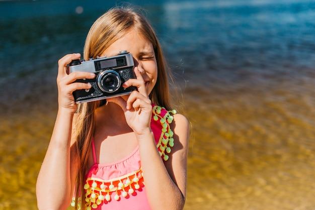 Ragazza che spara sulla macchina fotografica contro priorità bassa del mare Foto Gratuite