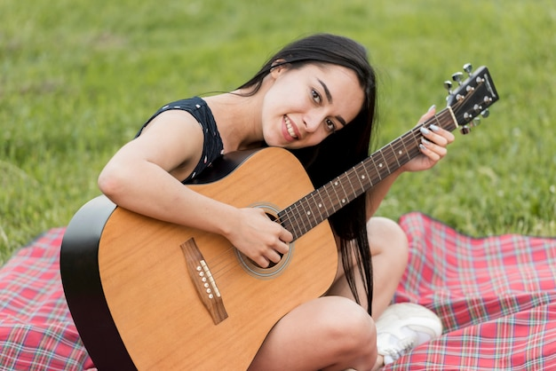 Ragazza che suona la chitarra su una coperta da picnic Foto Gratuite