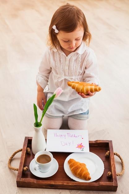 Ragazza che tiene croissant vicino al vassoio con biglietto di auguri Foto Gratuite
