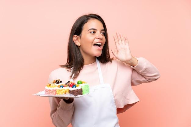 Ragazza che tiene i lotti di mini torte differenti sopra la parete isolata che grida con la bocca spalancata Foto Premium
