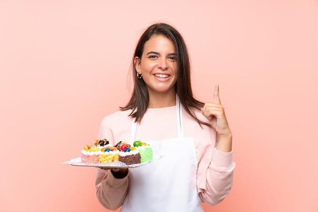 Ragazza che tiene i lotti di mini torte differenti sopra la parete isolata che indica su una grande idea Foto Premium