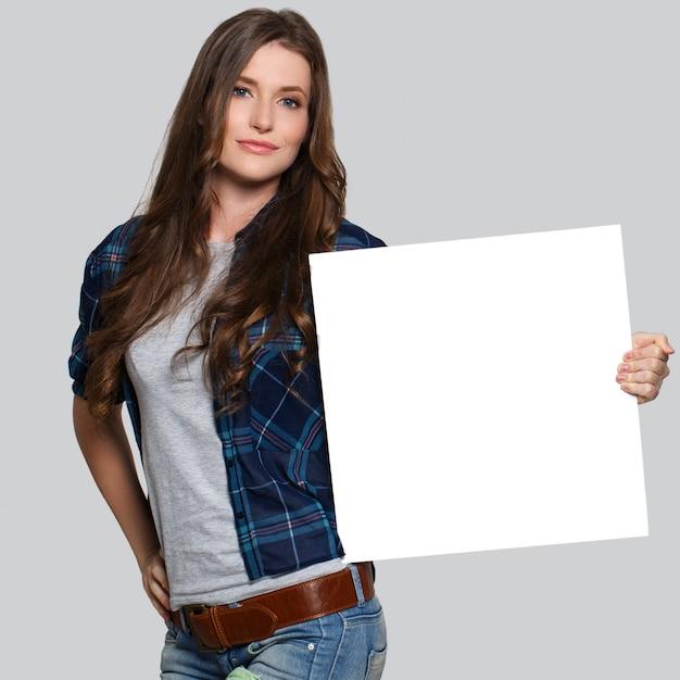 Ragazza che tiene tabellone per le affissioni bianco Foto Gratuite
