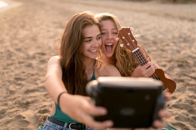 Ragazza che tiene ukulele in mano prendendo autoritratto dalla fotocamera istantanea in spiaggia Foto Gratuite