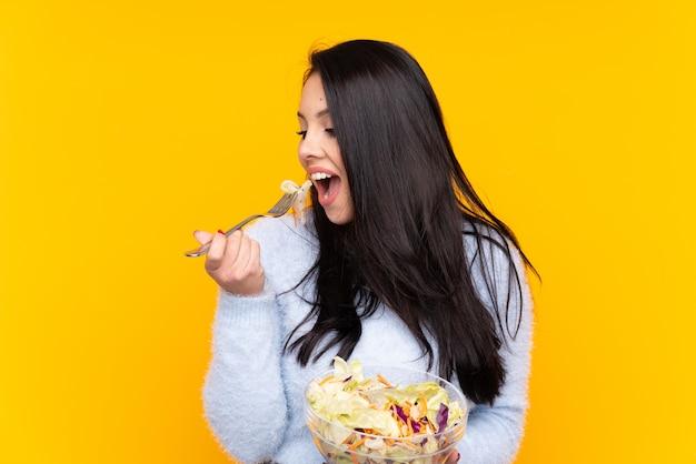 Ragazza che tiene un'insalata sopra la parete Foto Premium
