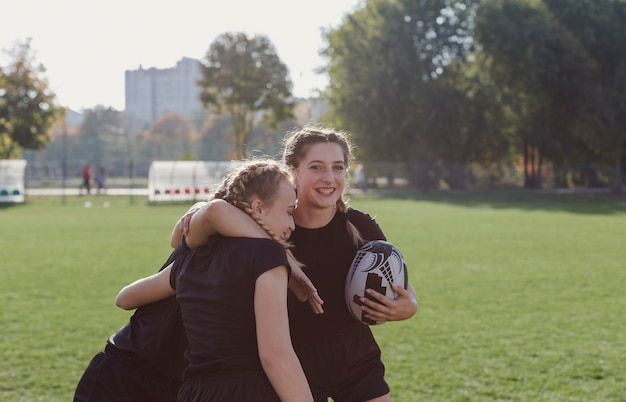Ragazza che tiene un pallone da calcio e che abbraccia i suoi compagni di squadra Foto Gratuite