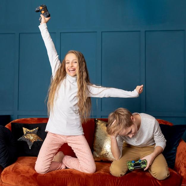 Ragazza che vince giocando ai videogiochi con suo fratello Foto Gratuite